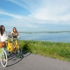 women walking with their bikes, Big Lake in the background