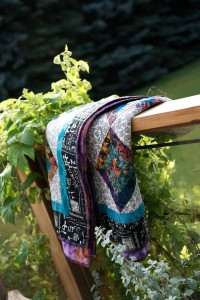 Colourful quilt hanging over deck railing