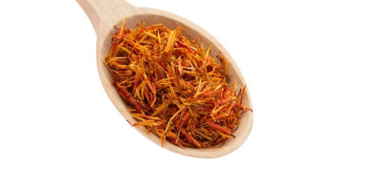 saffron spice in wooden spoon isolation white background