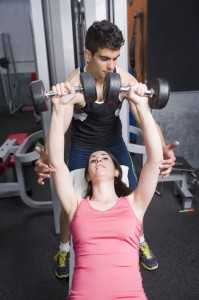 Man helping woman lift weights