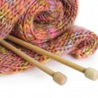 Knitting needles with finished garment