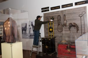 Archivist Vinothaan Vipulanantharajah making adjustments to the exhibition titled Weiller and Williams Co Ltd: Building a Livestock Empire.