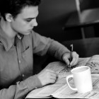 man at table writing, with coffee cup next to him